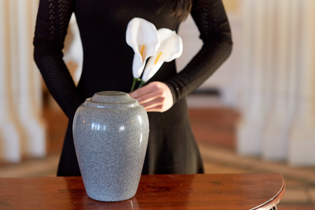 Foto de cremation, people and mourning concept - woman with flowers and cinerary urn at funeral in church - Imagen libre de derechos