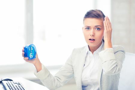 Foto de stressed businesswoman holding clock - Imagen libre de derechos