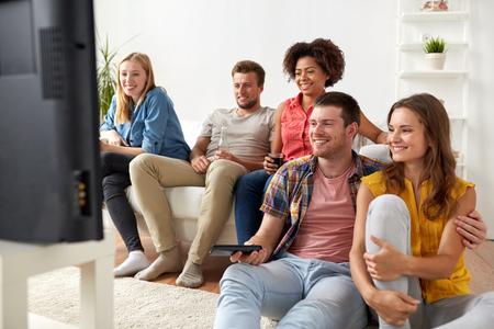 Foto de happy friends with remote watching tv at home - Imagen libre de derechos