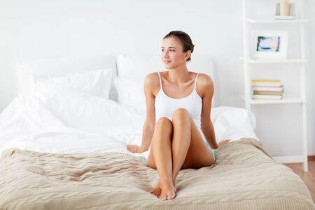 Foto de beautiful woman with bare legs on bed at home - Imagen libre de derechos