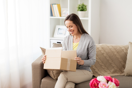 Foto de smiling woman opening cardboard box - Imagen libre de derechos