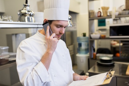 Foto de chef calling on smartphone at restaurant kitchen - Imagen libre de derechos