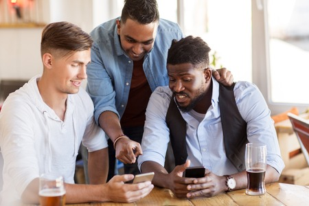 Photo pour male friends with smartphone drinking beer at bar - image libre de droit