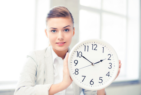 Photo pour attractive businesswoman showing white clock - image libre de droit