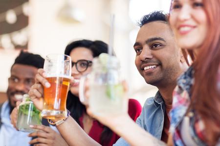 Foto de happy friends with drinks at restaurant - Imagen libre de derechos