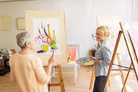 Photo for Artist women with easels painting at art school - Royalty Free Image