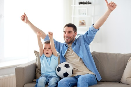 Foto de father and son watching soccer on tv at home - Imagen libre de derechos