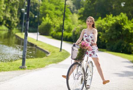 Photo pour happy woman riding fixie bicycle in summer park - image libre de droit