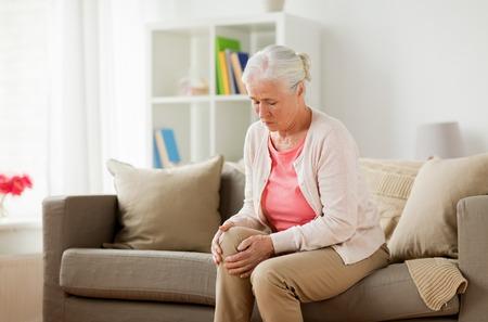 Foto de senior woman suffering from pain in leg at home - Imagen libre de derechos