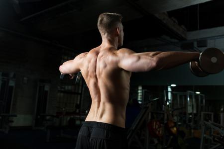 Photo pour close up of man with dumbbells exercising in gym - image libre de droit