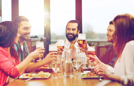 Photo pour friends dining and drinking beer at restaurant - image libre de droit