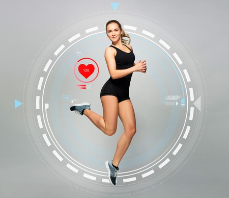 Photo for young woman in black sportswear jumping with pulse - Royalty Free Image