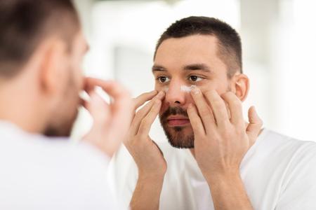 Photo pour young man applying cream to face at bathroom - image libre de droit