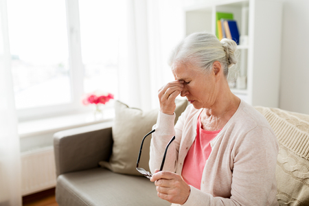 Photo pour senior woman with glasses having headache at home - image libre de droit