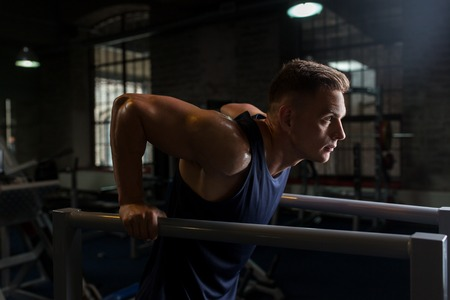 Photo for man doing triceps dip on parallel bars in gym - Royalty Free Image