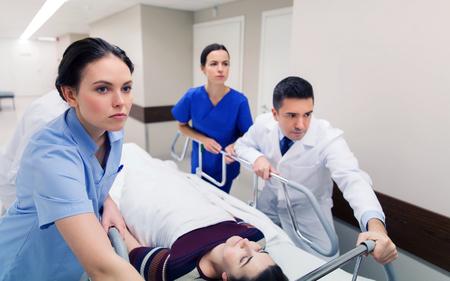 Foto de medics with woman on hospital gurney at emergency - Imagen libre de derechos