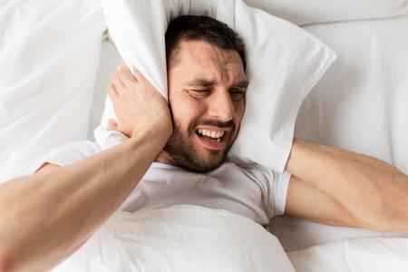 Foto de man in bed with pillow suffering from noise - Imagen libre de derechos