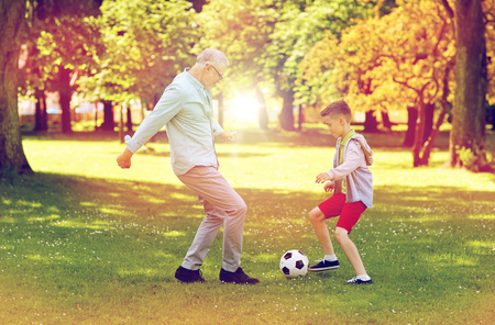 Photo pour old man and boy playing football at summer park - image libre de droit