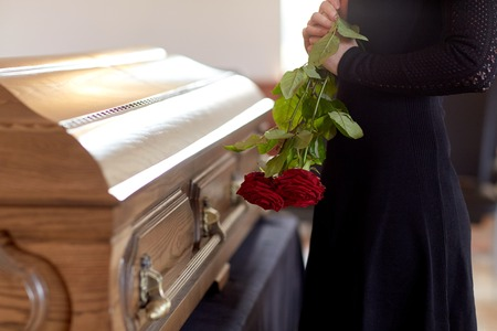 Photo for woman with red roses and coffin at funeral - Royalty Free Image