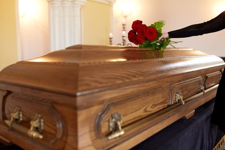 Photo pour woman with red roses and coffin at funeral - image libre de droit