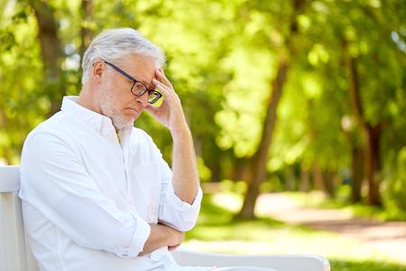 Foto de thoughtful senior man sitting at summer park - Imagen libre de derechos