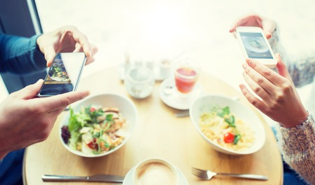 Photo pour close up of couple picturing food by smartphone - image libre de droit