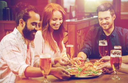 Photo pour friends eating pizza with beer at restaurant - image libre de droit