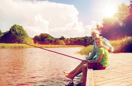 Photo pour grandfather and grandson fishing on river berth - image libre de droit