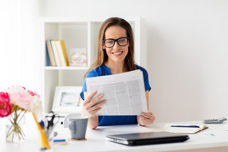 Photo for happy woman in glasses reading newspaper at office - Royalty Free Image
