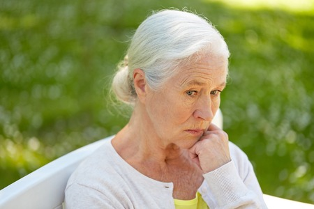 Foto de sad senior woman sitting on bench at summer park - Imagen libre de derechos