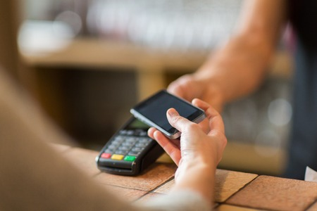 Photo pour hands with payment terminal and smartphone at bar - image libre de droit