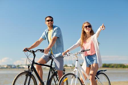 Photo pour happy young couple riding bicycles at seaside - image libre de droit