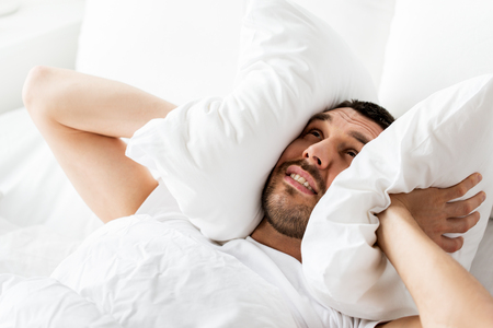 Foto de Man in bed with pillow suffering from noise - Imagen libre de derechos