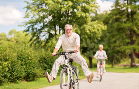 Foto de happy senior couple riding bicycles at summer park - Imagen libre de derechos