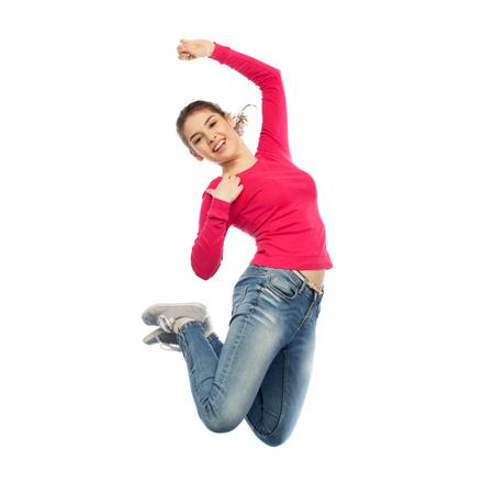 Foto de smiling young woman jumping in air - Imagen libre de derechos