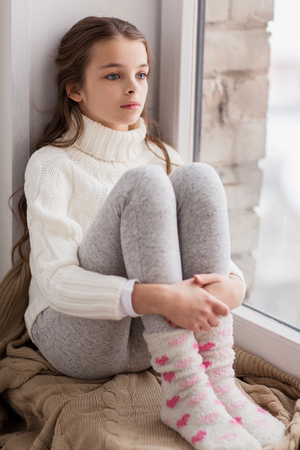 Photo for sad girl sitting on sill at home window in winter - Royalty Free Image