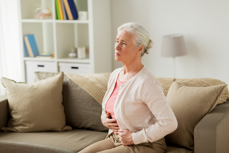 Photo pour senior woman suffering from stomach ache at home - image libre de droit