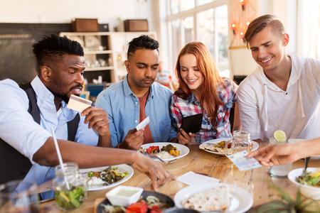 Foto de happy friends with money paying bill at restaurant - Imagen libre de derechos