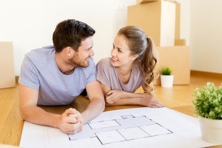Photo pour couple with boxes and blueprint moving to new home - image libre de droit