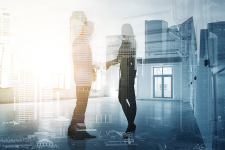 Foto de business, partnership and cooperation concept - businessman and businesswoman silhouettes shaking hands over city background - Imagen libre de derechos