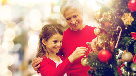 Foto de winter holidays, family and people concept - happy grandmother and granddaughter decorating christmas tree over lights background - Imagen libre de derechos