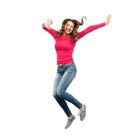 Foto de happiness, freedom, motion and people concept - smiling young woman jumping in air over white background - Imagen libre de derechos