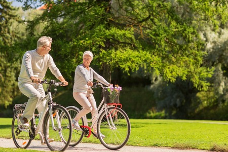 Photo for active old age, people and lifestyle concept - happy senior couple riding bicycles at summer park - Royalty Free Image