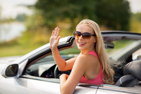 Foto de travel, road trip and people concept - happy young woman in convertible car waving hand - Imagen libre de derechos