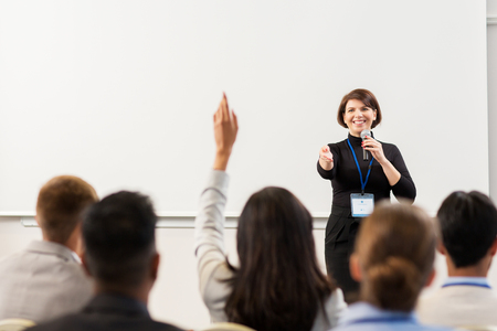 Foto de business, education and people concept - smiling businesswoman or teacher with microphone answering questions at conference presentation or lecture - Imagen libre de derechos