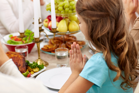 Photo pour girl with family having dinner and praying at home - image libre de droit