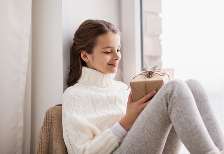 Photo pour girl with christmas gift sitting at home - image libre de droit