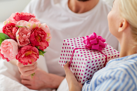Photo pour close up of couple with gift and flowers in bed - image libre de droit