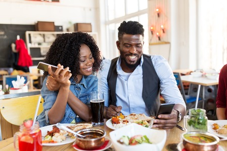 Photo pour happy man and woman with smartphones at restaurant - image libre de droit