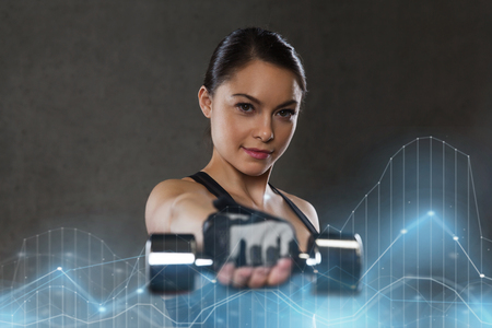 Photo pour fitness, sport, exercising, training and people concept - young woman flexing muscles with dumbbells in gym - image libre de droit